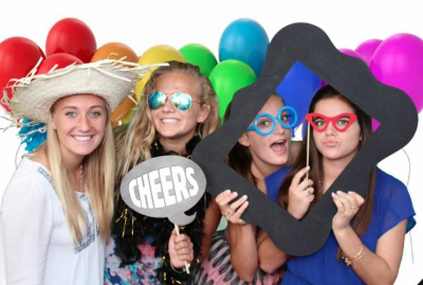 4 girls holding fun props in a Shutterbug Photo Booth